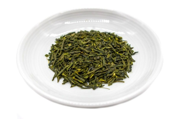 Needle-shaped and deep green premium organic gyokuro leaves from Saga, Japan, in a small round white dish.