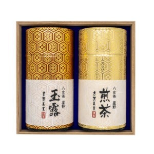 Front view of two shiny golden tube-shaped green tea boxes placed inside a wooden box with Japanese hand-written calligraphy on their labels marking their contents (Yame gyokuro and Yame sencha).