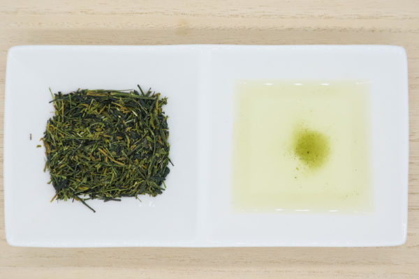 Top view of a rectangular porcelain dish, with one square filled with needle-shaped leaves of Japanese premium white tea from Yame, and the other with pale-white brewed white tea.
